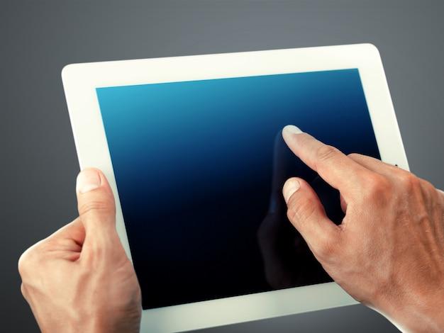 Doigt d'homme d'affaires pointant sur une tablette numérique à écran tactile sur fond