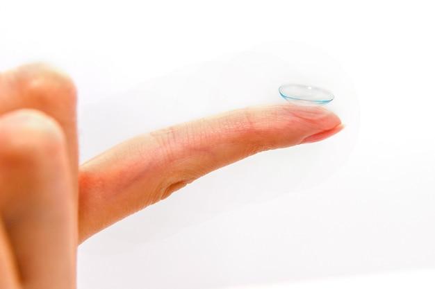 Doigt avec lentilles de contact isolé sur fond blanc