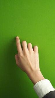 Doigt et main de femme et toucher sur fond d'écran vert.