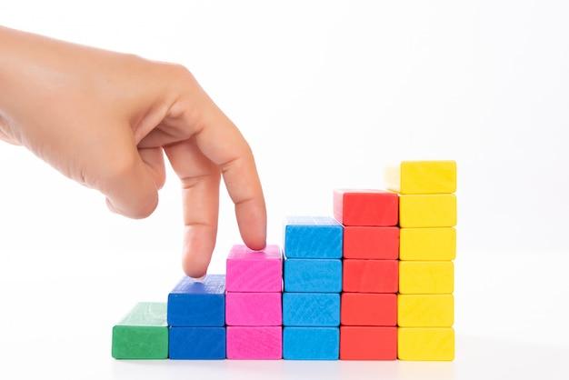 Le doigt de la main marche sur un bloc de bois empilé comme un escalier. concept de croissance d'entreprise.
