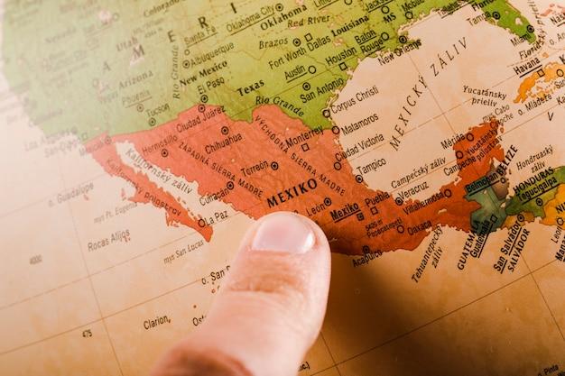 Le doigt d'une personne montrant la ville de mexico sur la carte