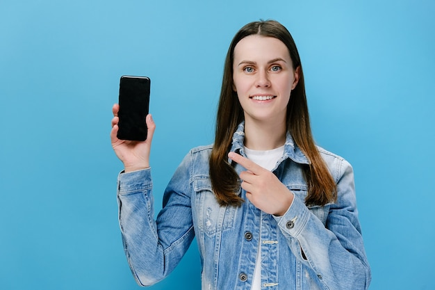 Doigt de point de femme au téléphone portable d'écran vide