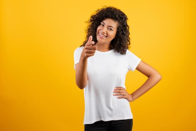 Doigt pointé de belle femme africaine noire isolée sur jaune