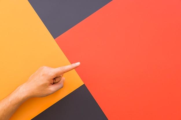 Le doigt pointe vers le haut en arrière-plan géométrique