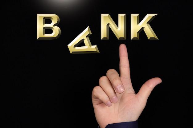 Un doigt pointe vers le mot bank avec la lettre a tombant sur un fond noir