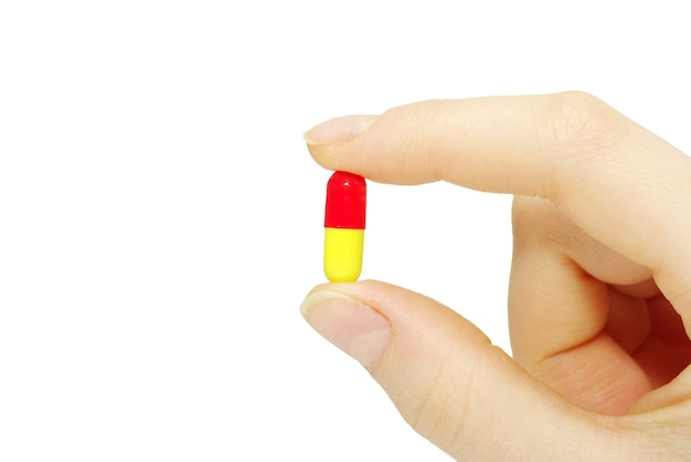 Doigt tient la pilule isolé sur blanc