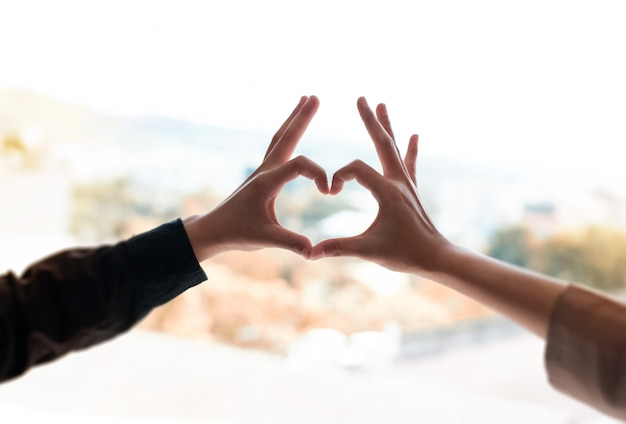 Doigts de contact humain ensemble, formant une forme de cœur, signe et symbole de l'amour, lumière floue autour