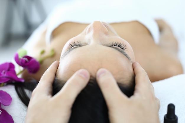 Les doigts du masseur se trouvent sur le visage de femme gros plan