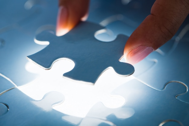 Doigts femelles correspondant à la dernière pièce du puzzle blanc. image conceptuelle du bâtiment et bouton vers le haut.