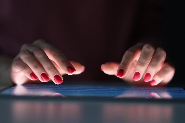 Doigts féminins sur l'écran de la tablette pendant la nuit. concept de journée de travail irrégulière