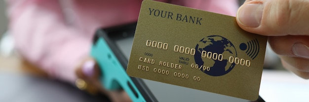 Les doigts mâles détiennent la carte de crédit au-dessus du terminal