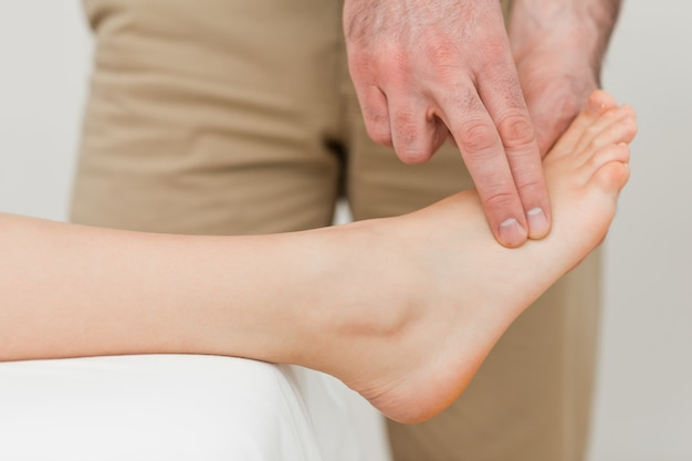 Doigts d'un physiothérapeute appuyant sur un pied