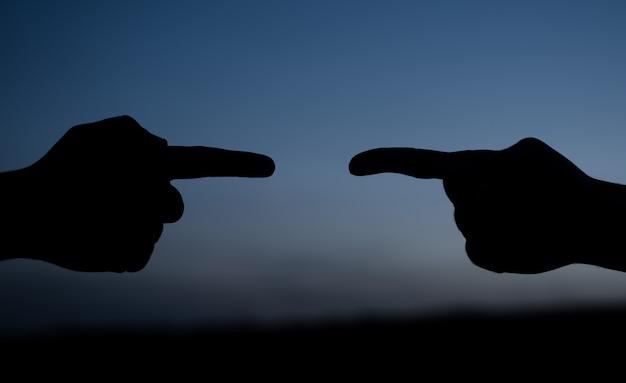 Les doigts se pointent l'un sur l'autre silhouette en plein air