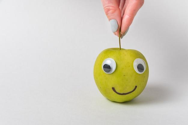 Doigts tenant une pomme pour la tige. smiley aux pommes avec grimace sur fond blanc.