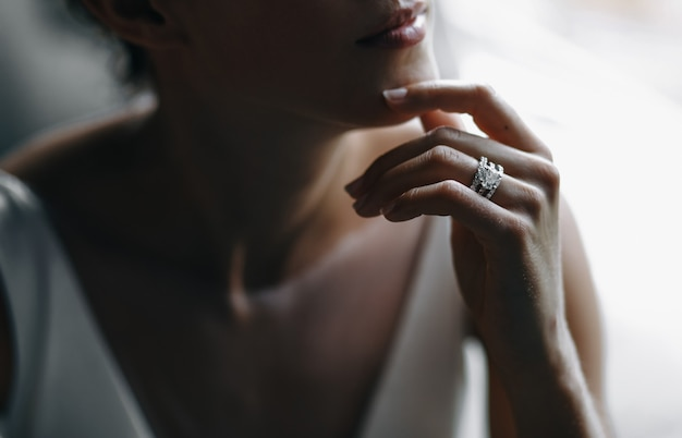 Les doigts tendres de la mariée touchent son menton