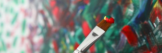 Les doigts tiennent le pinceau avec de la peinture dans la peinture avant