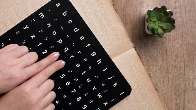 Doigts touchant le tableau de l'alphabet braille