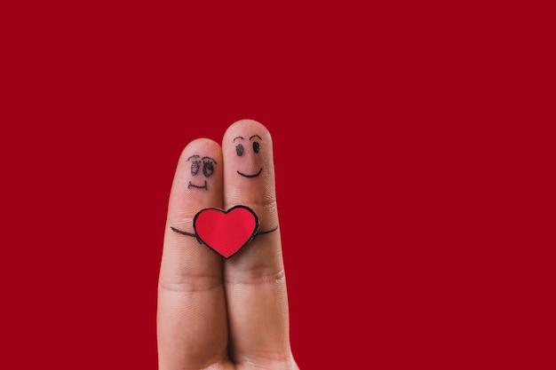 Les doigts avec des visages dessinés et un cœur au milieu