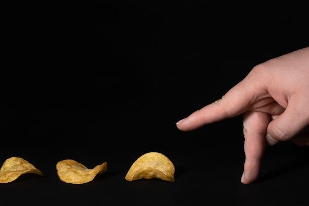 Les doigts vont pour les chips chips track sur fond noir