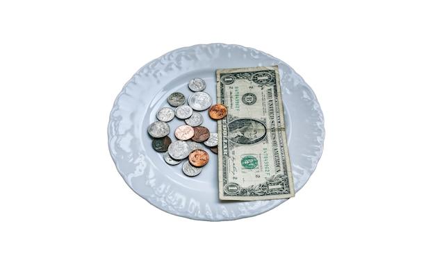 Un dollar allongé sur la plaque isolé sur fond blanc. pas de photo d'argent. idée des pauvres. pièces de dix cents et cents. petit salaire et pension pas assez pour la nourriture. problèmes sociaux.