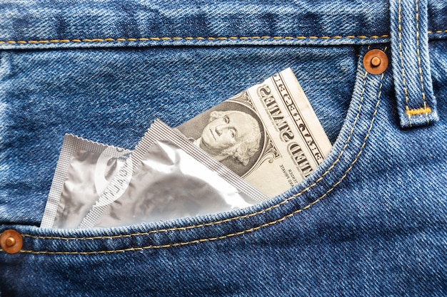 Dollar américain et préservatif dans la poche avant droite d'un jean bleu