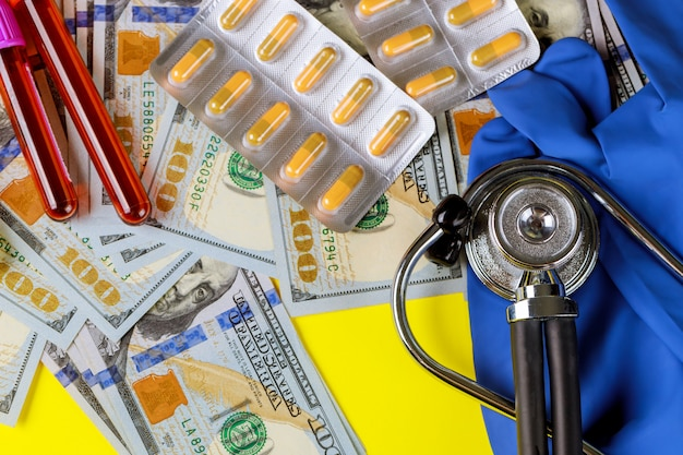Dollar d'argent avec des comprimés sous blister sur un tube à essai de sang stéthoscope