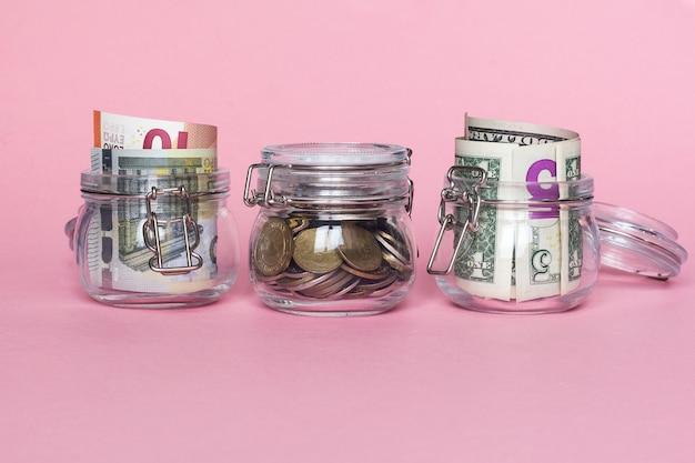 Dollar, euro et pièces en pot de verre sur fond rose. concept d'économie d'argent