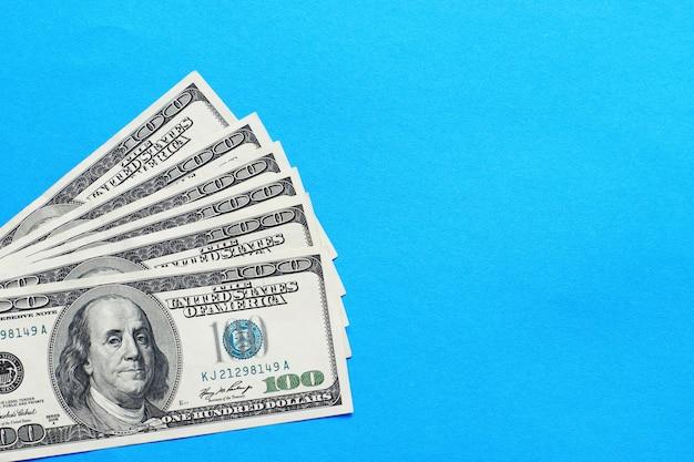 Dollars américains en billets de cent dollars sur fond bleu.