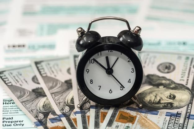 Dollars américains avec horloge sur formulaire fiscal individuel