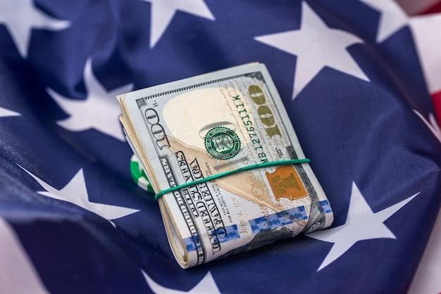 Dollars américains en tas sur le drapeau national