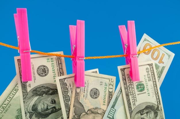 Dollars argent sur corde à linge sur fond bleu