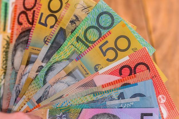 Dollars australiens en ventilateur sur un bureau en bois
