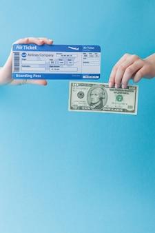 Dollars et billet d'avion en main de femme sur fond bleu. concept de voyage, espace copie