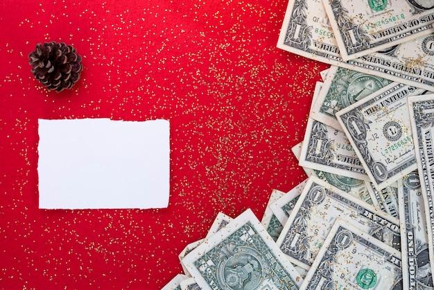 Dollars bills over red avec pomme de pin et note vide