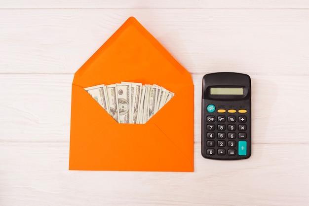 Dollars dans une enveloppe orange et une calculatrice sur un fond en bois blanc.