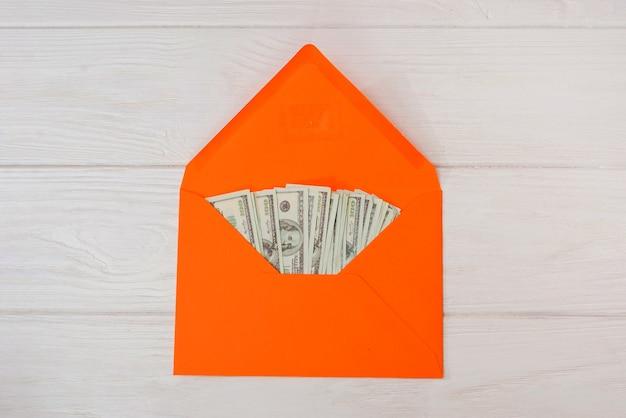 Dollars dans une enveloppe orange sur un fond en bois blanc.