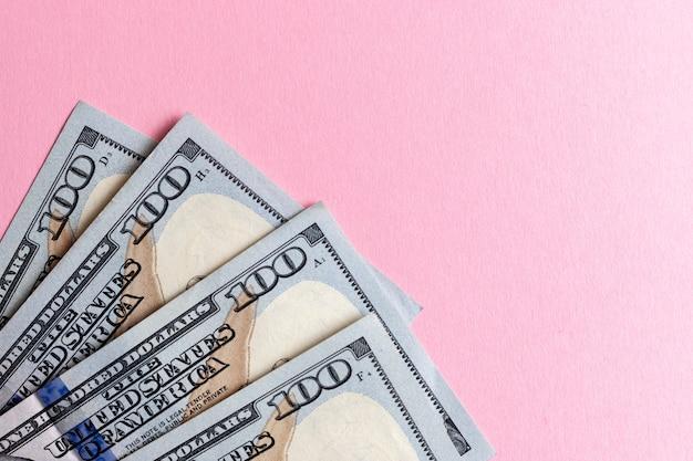 Dollars en espèces sur fond rose.