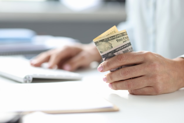 Dollars en main de femme et clavier d'ordinateur sur table. gagner de l'argent sur le concept internet