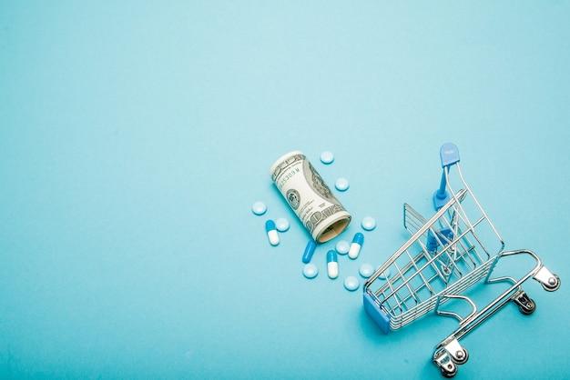 Dollars, pilules et panier sur fond bleu. concept de pharmacie. copier l'espace
