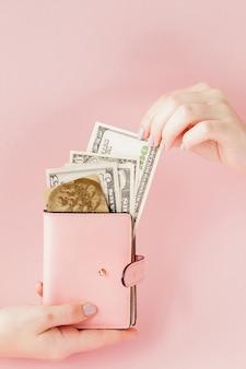 Dollars et portefeuille rose avec carte de crédit dans les mains de la femme sur fond rose