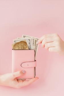 Dollars et portefeuille rose avec carte de crédit dans les mains de la femme rose.