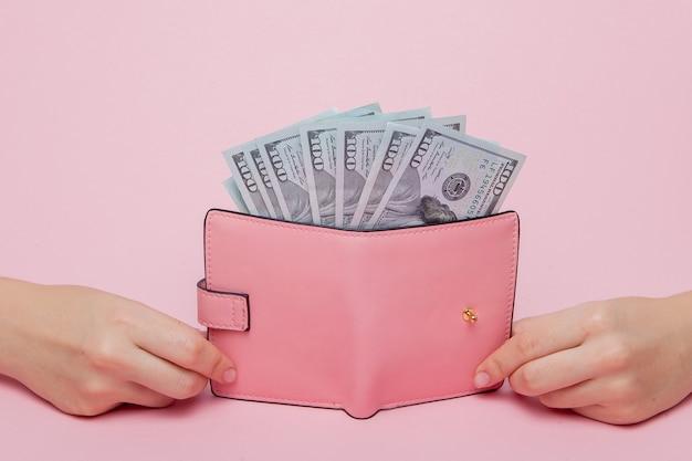 Dollars et portefeuille rose dans la main de la femme