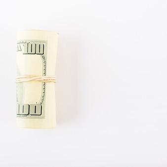 Dollars roulés dans un tube sur fond blanc