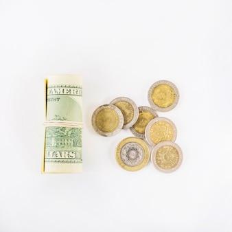 Dollars roulés et pièces de monnaie sur table