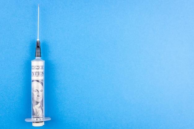 Dollars et seringue médicale