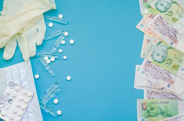 Dollars de singapour et comprimés, ampoules avec médicament, masque
