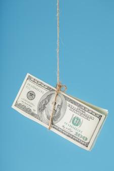 Les dollars sont attachés sur une corde, sur un bleu.