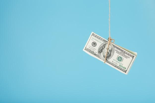 Les dollars sont attachés sur une corde, sur du bleu. isolez, espace libre.