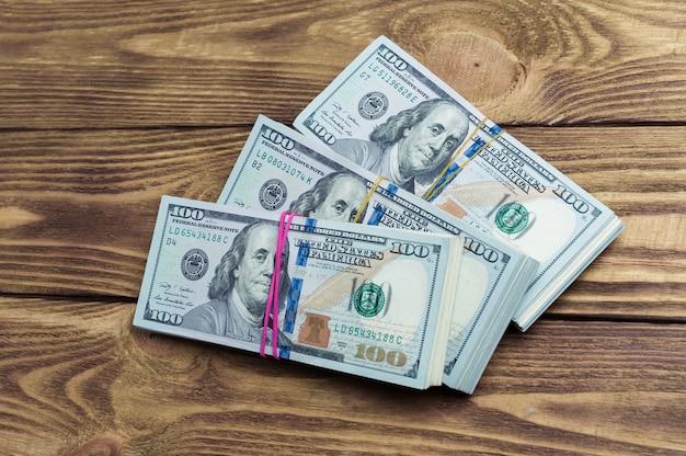 Dollars en trois paquets sur une table en bois.