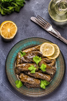 Dolma, feuilles de vigne farcies avec du riz et de la viande sur fond sombre, vue de dessus.